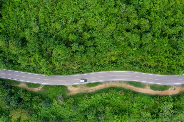 上空から見た雨季の緑の山の森と田舎を結ぶ丘の上の曲がった道