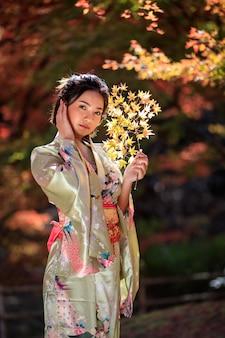 公園で日本の金の着物を着ているアジアの女性の美しい肖像画