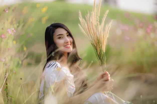 座っている肖像画アジアの美しい女性がフラワーガーデンでリラックス
