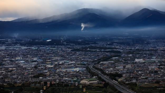 日本のストロムとスモッグレイヤーの山背景の劇的で暗いプロセスの街並み