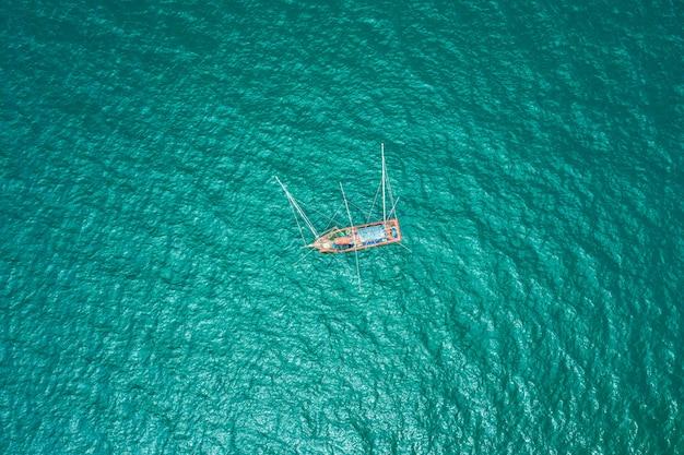 Рыбацкая лодка на зеленом море с высоты птичьего полета