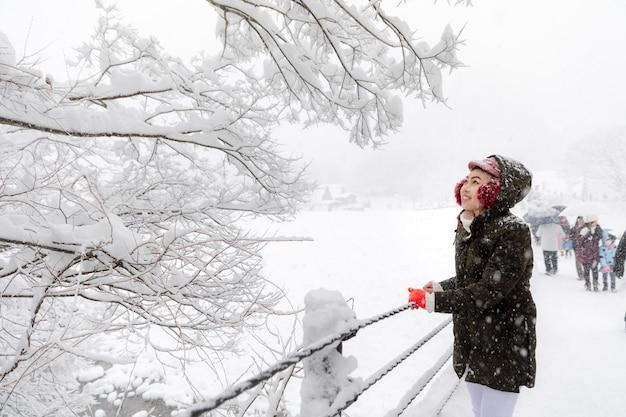 冬の雪の季節に若いアジア女性の女の子