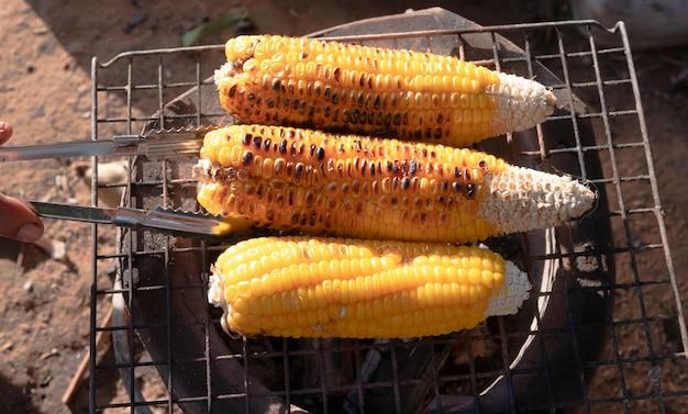 手はストーブの炭にトウモロコシを反転