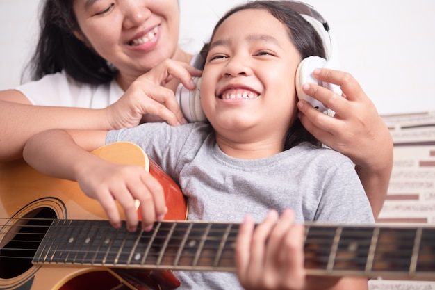 お母さんは小さな女の子のために白いヘッドフォンをかぶっていた