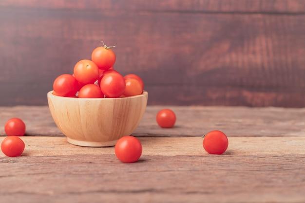 木製テーブルの上のボウルの場所でチェリートマト