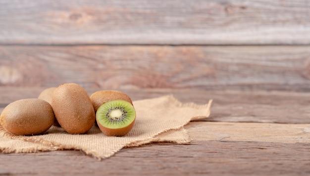キウイフルーツと木製のテーブルの上の袋の場所に半分