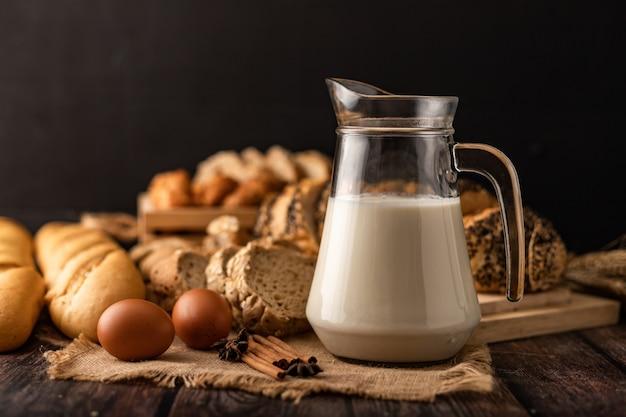 食材を使った木製のテーブルに置かれたガラス瓶のミルク
