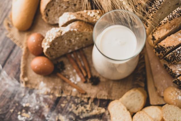 食材を使った木製のテーブルに置かれたガラス瓶の中のトップビューミルク