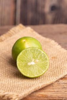 緑のライムの半分を閉じ、キッチンの木製テーブルの上の編まれた袋の種子の場所