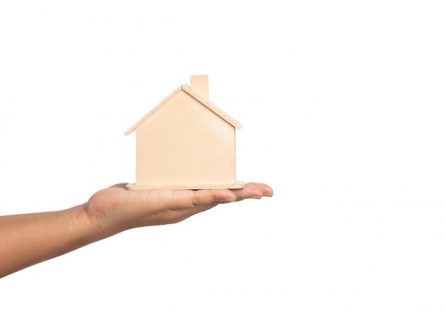 白で隔離される女性の手に小さな家モデル