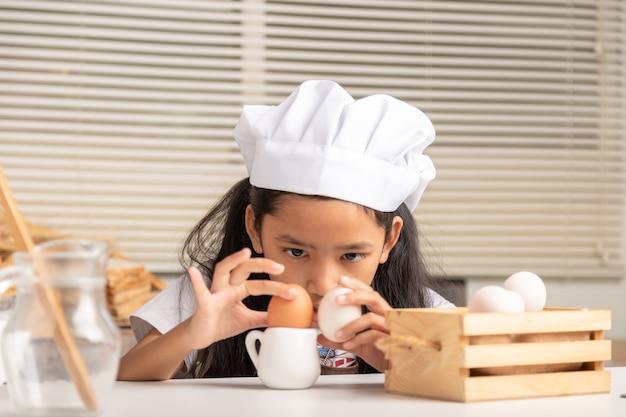 Маленькая азиатка в белой шляпе от шеф-повара смотрит на яйца на маленьком кувшине