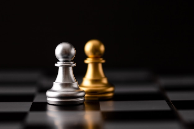 Золотая и серебряная фишка на шахматной доске