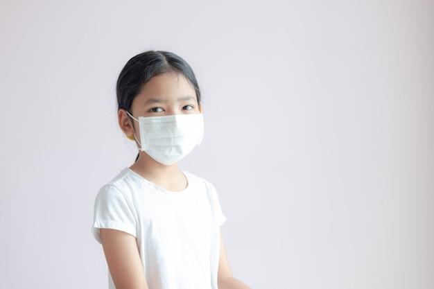 Портрет маленькой азиатской девушки носит медицинскую защитную маску.