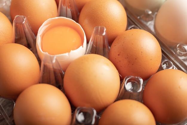 木製のテーブルの上のプラスチックの箱にアヒルの壊れた卵