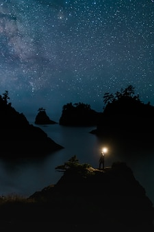 星と光で立っている旅行者と夜の秘密のビーチオレゴン