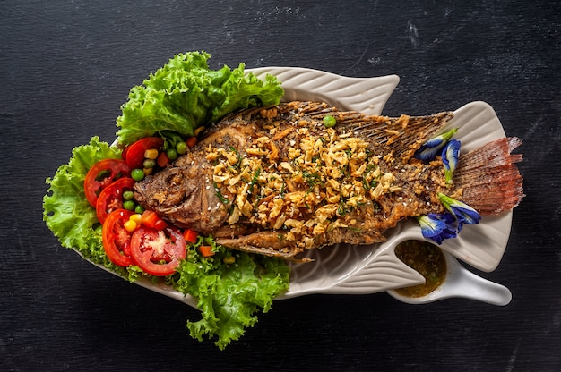 白い皿に野菜と揚げ魚。上面図