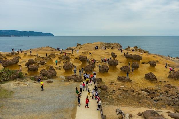 Многие туристы смотрят каменный странный облик в геопарке йелиу, новый тайбэй, тайвань.