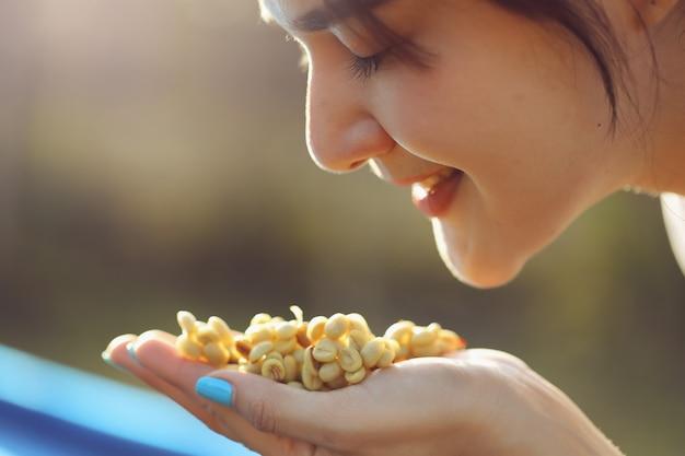 Бариста женского пола осматривает высушенные кофейные зерна путем обоняния перед жаркой. она счастлива со свежестью кофейных зерен.