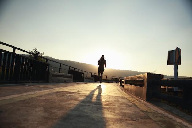 夕方、若いランナーが滑走路を走ります。健康的なジョギングの概念(シルエット)