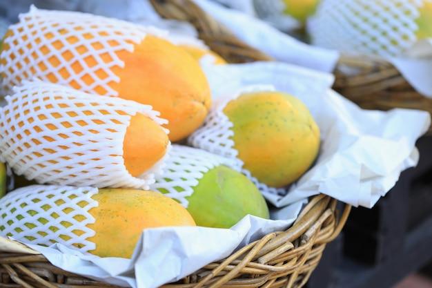 店の前に置かれたバスケットの夏の果物。かごの中の熟したパパイヤ