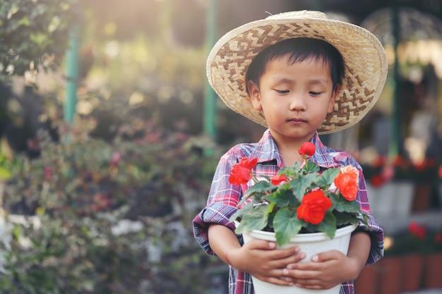 アジアの少年が立ち上がって、木の店の前にバラの鉢を持ちました。