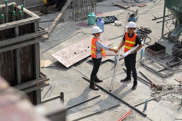 Два строительных инженера пожимают друг другу руки на строительной площадке