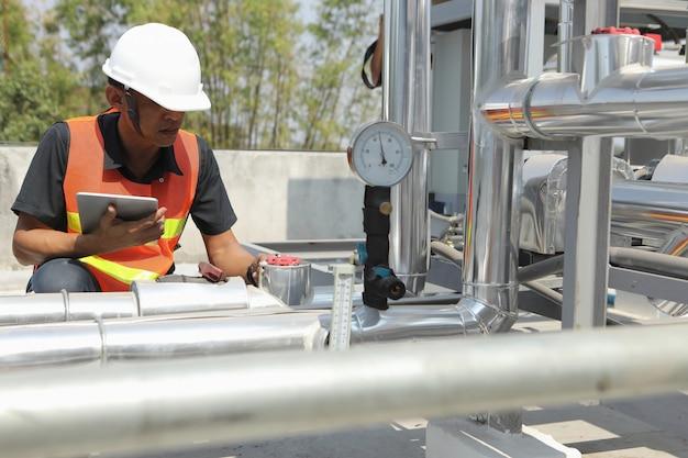 システムエンジニアは圧力をチェックし、タブレットで記録しています。