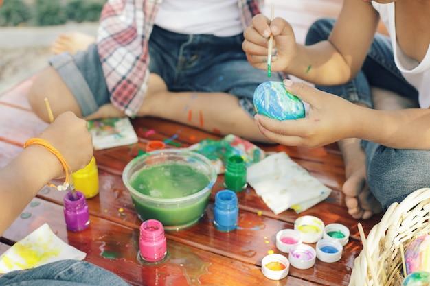 Дети веселятся, раскрашивая яйца на пасху.