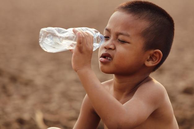 アジアの少年は現在、消費するためのきれいな水が不足しています。