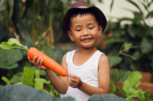 Азиатский мальчик взволнован морковным продуктом, который он посадил. концепции обучения вне класса