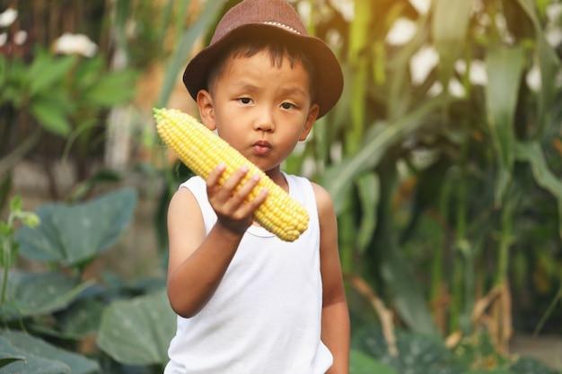 Азиатский мальчик взволнован посевами кукурузы, которые он посадил. концепции обучения вне класса