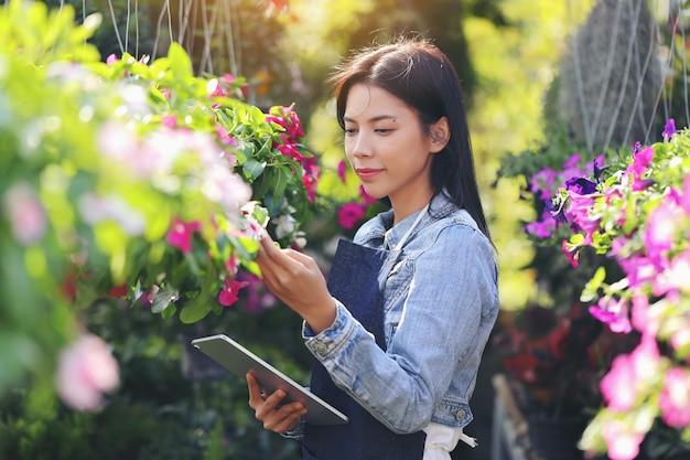 Азиатская женщина, владеющая бизнесом цветочного сада, считает, что цветы соответствуют заказу клиента.