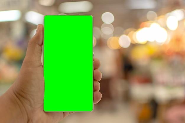 Мужчина держит телефон с зеленым экраном