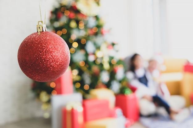 部屋の中に赤い装飾が施された緑のクリスマスツリー。