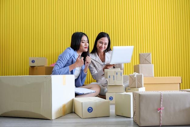 彼女の周りの箱に座っている美しいアジアの実業家。