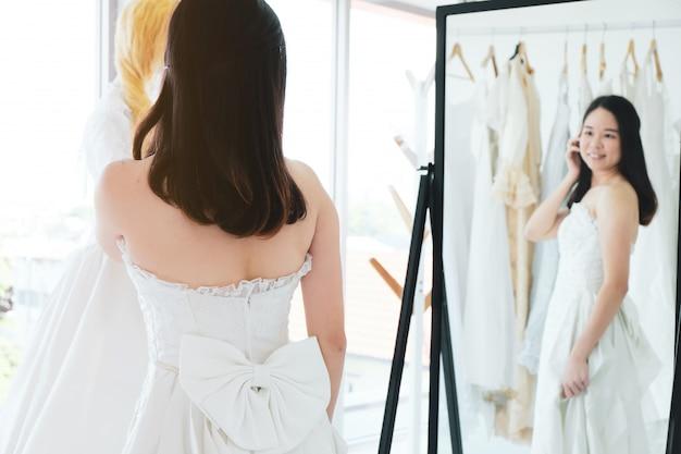 美しいアジアの女の子は、店でブライダルドレスを試してみてください。