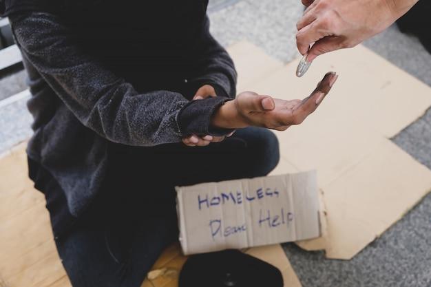 一人で物乞いを座っている若い男