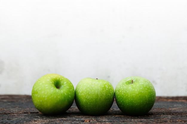 Три свежие зеленые яблоки на дереве