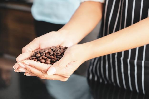 乾燥茶色のコーヒー豆は若い従業員の手の中にあります。
