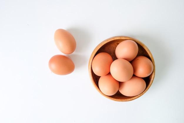 白い木製のテーブル背景に置かれた農場からの新鮮な卵
