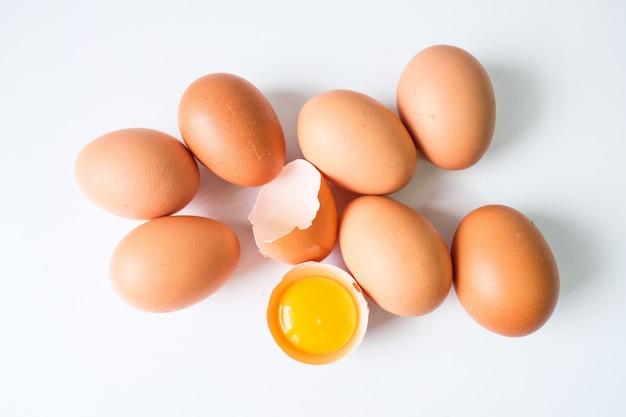 白い木製のテーブルに置かれた農場からの新鮮な卵