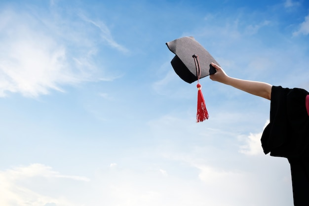 彼女の手、帽子、証明書の腕で立っている黒いローブの美しい若い学生。