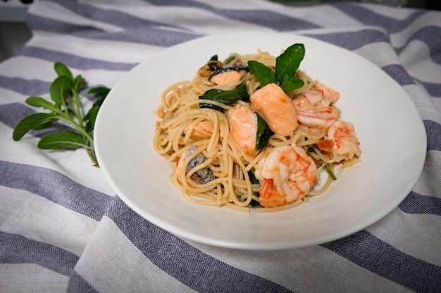 木製テーブルの上の白いボウルにサーモン、エビ、胃のスパゲッティ炒め