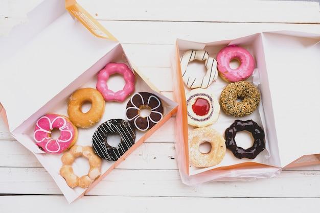 Разные пончики оба с белым шоколадно-розовым покрытием, рисунок