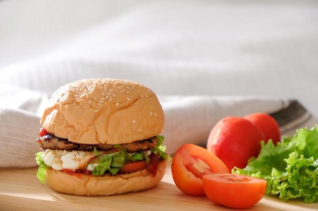 Бургеры с сыром, салатами и овощами на белом пространстве