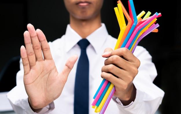 Знак руки бизнесмена говорит нет пластиковым соломкам, люди запрещают и прекращают использовать пластиковый мусор