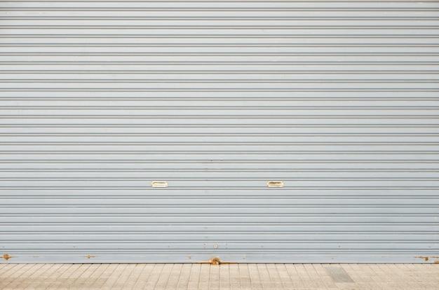 コンクリートタイル張りの床と大きなガレージ倉庫の入り口のローリングシャッタードア