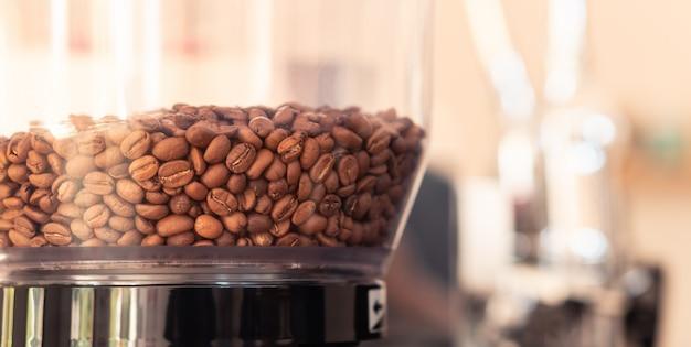 カフェでの朝のコーヒーカップのための粉を作るために焙煎機でコーヒー豆