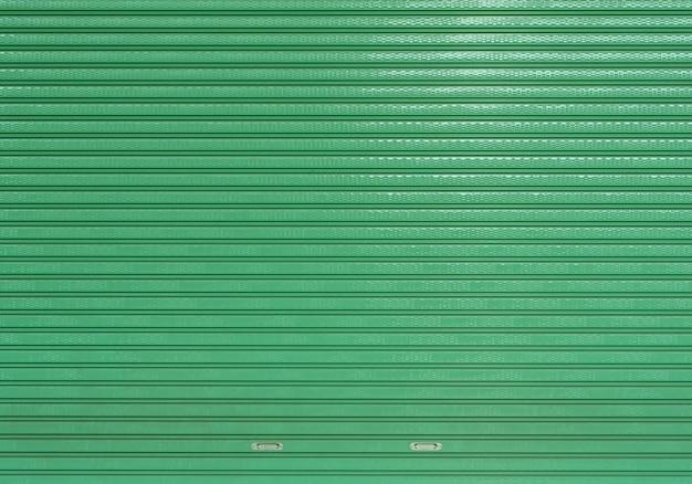 緑の空のきれいなローラーシャッタードア倉庫、車のガレージストア入り口の背景の金属板のテクスチャを剥奪