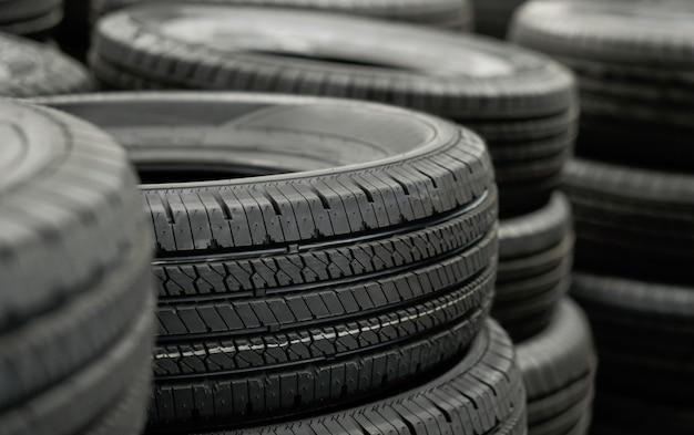 ディストリビューターへの輸送を待っている倉庫のタイヤスタックの山、製造工場での新しい車のタイヤ製品